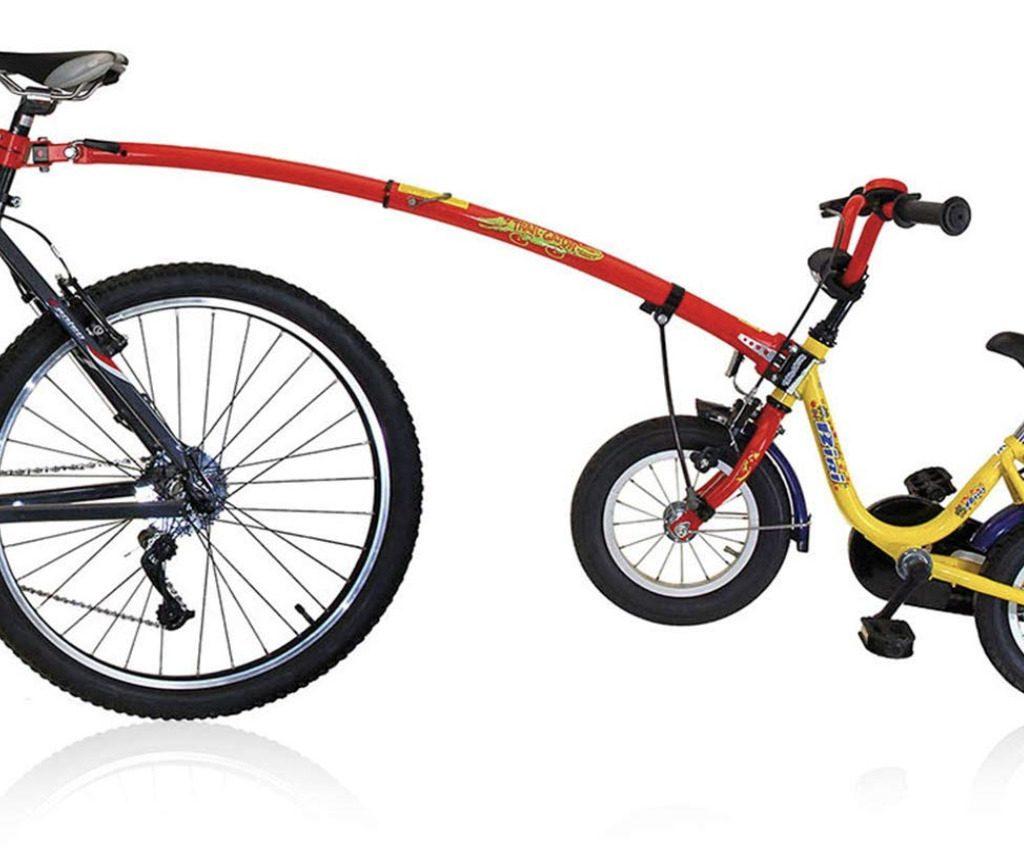 Bicicleta del adulto y bicicleta del niño conectadas por la barra de remolque Trail Gator