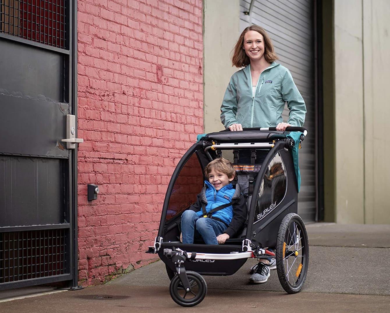 madre empujando el remolque bicicleta como cohecito de paseo Encore X