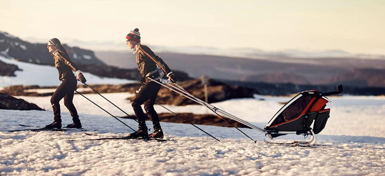 Padres en la nieve tirando del remolque infantil para bicicletas Thule Chariot Cross
