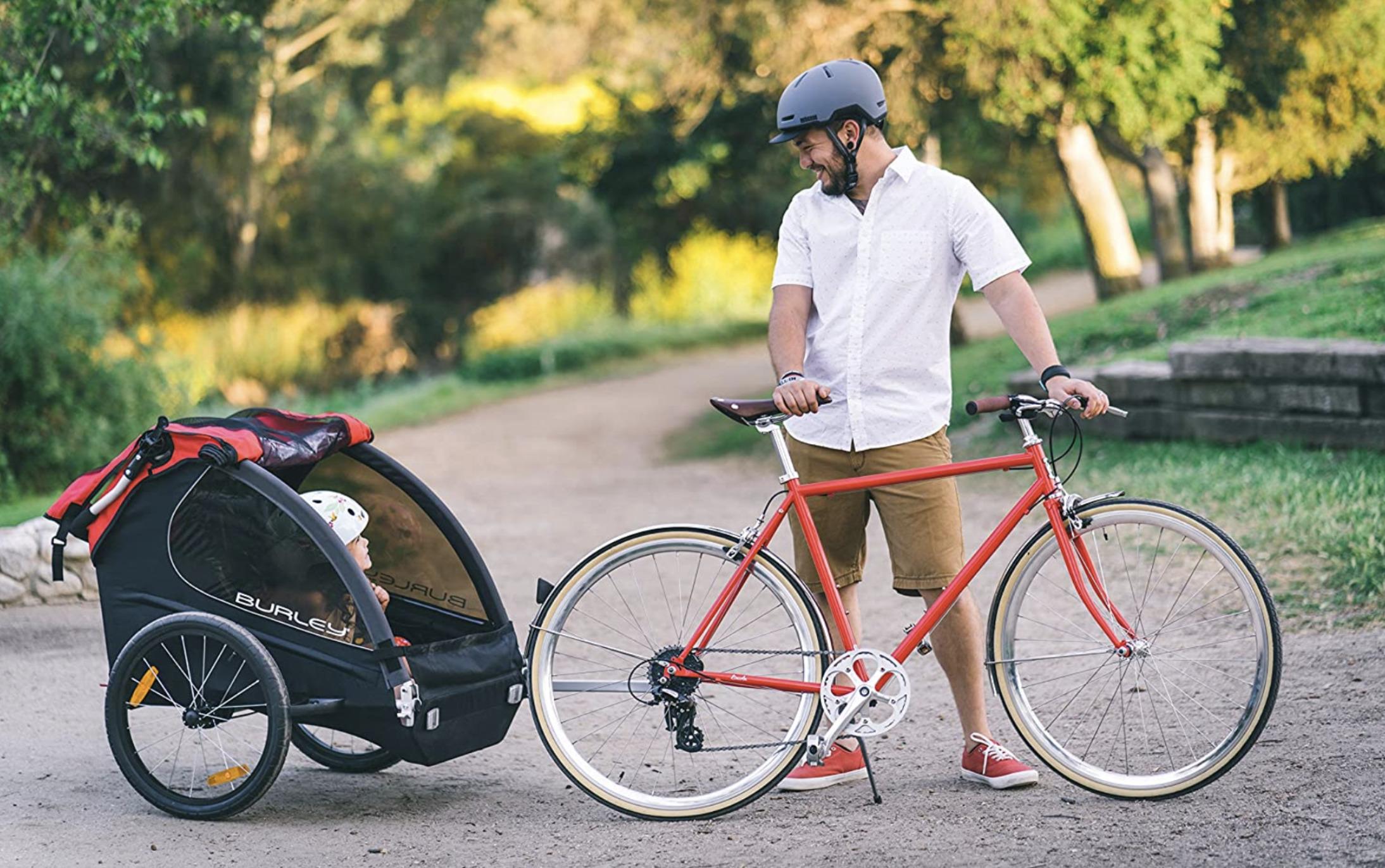 Padre llevando a su hijo en remolques de bicicletas para niños Burley