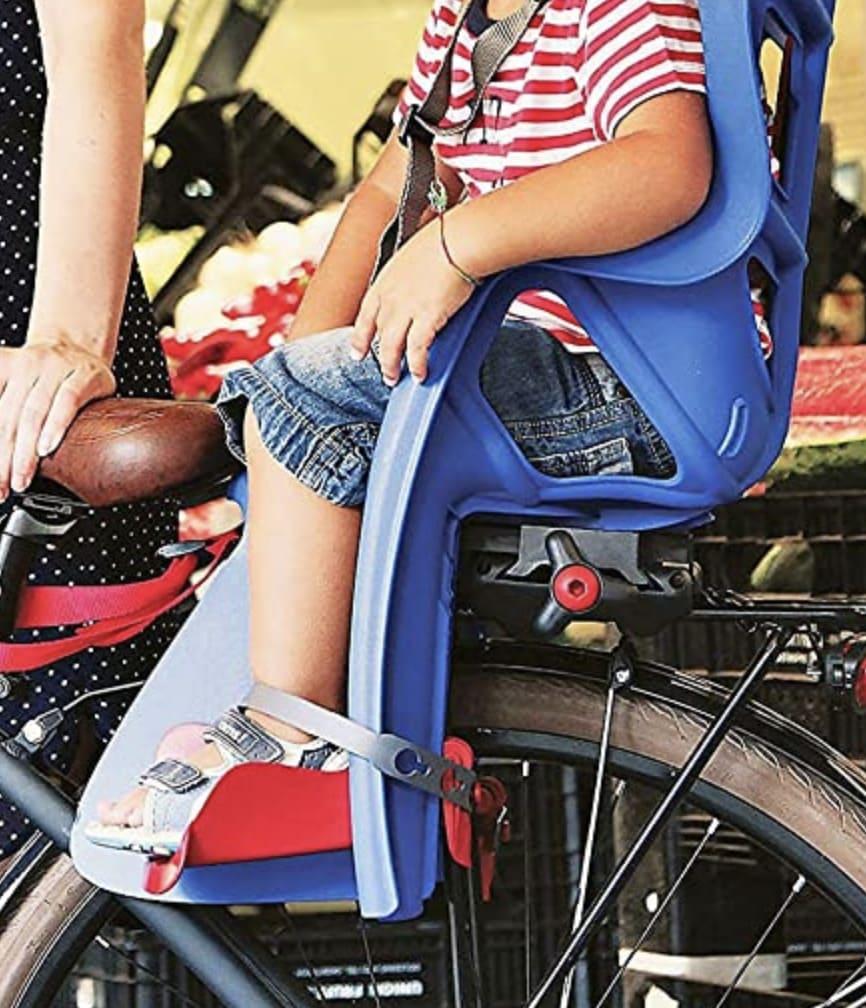 Nila montada sobre su asiento de bicicleta Bellilli Pepe con las correas de los pies ajustadas