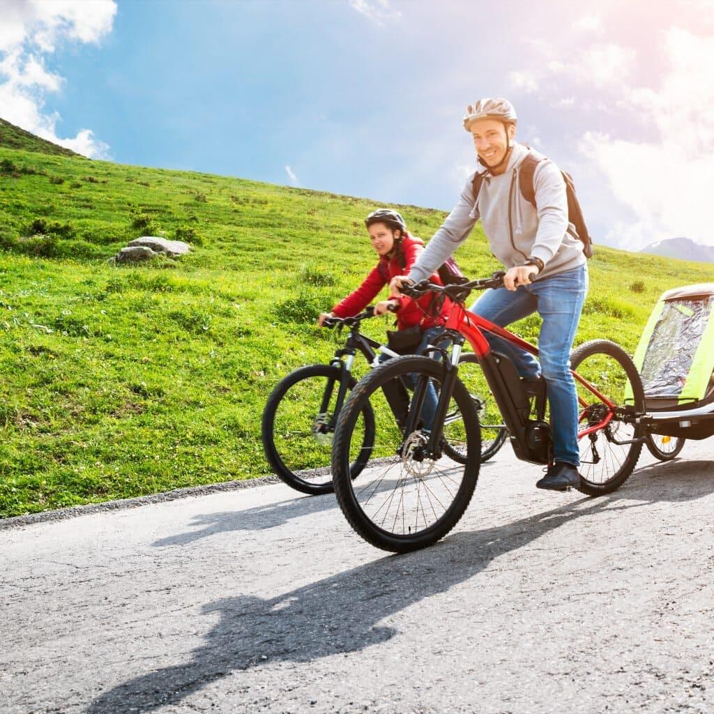 Padre y madre en bicicleta paseando mientras remolcan a su hijo con un remolque de bicicleta para niños