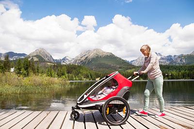 Señora llevando a su hija dentro del remolque de bicicleta Hamax Outback en modo cochecito de paseo