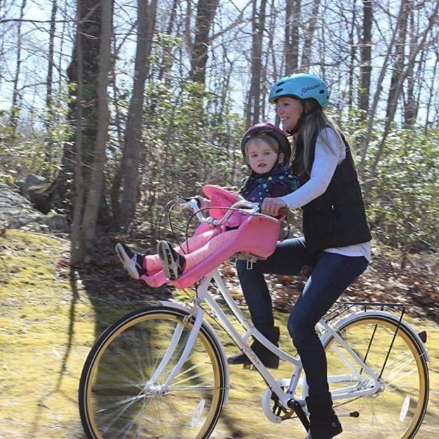 Madre llevando a su bebé en su bicicleta montado en un asiento delantero iBert color rosa