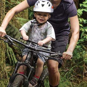 Madre llevando a su hijo en su bici de montaña montado e el asiento delantero Shotgun