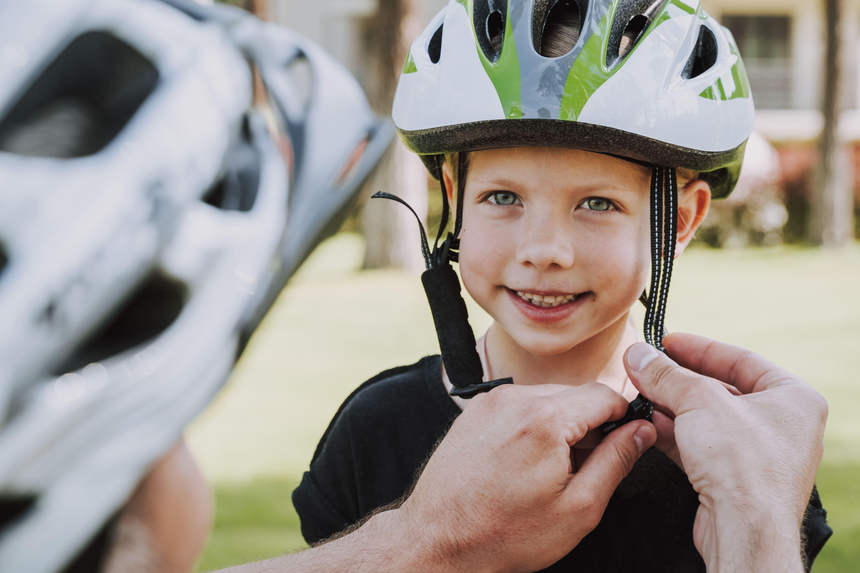 Madre abrochando el casco de bicicleta a su hija