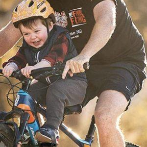 Padre llevando a su hijo en el asiento delantero para bicics de montaña Kids Ride Shotgun