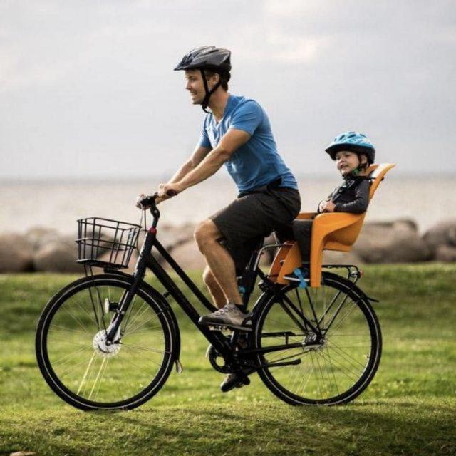 Padre llevando a su hijo en su bici con un asiento de bicicleta para niños instalado en la parte trasera