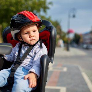 Bebé con un casco montado en una sillita para bicicleta