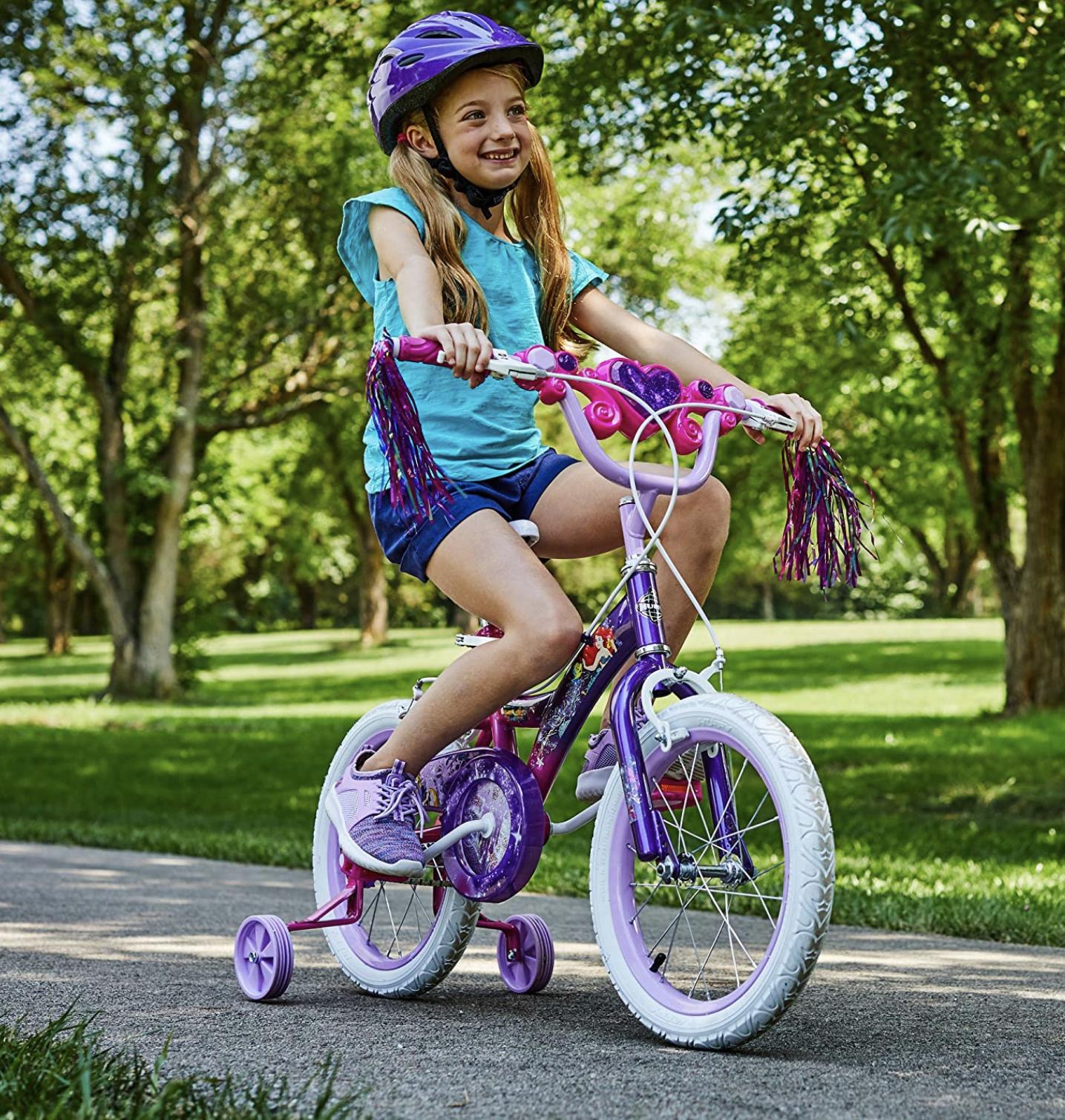 niña conduciendo su bicicleta de cuatro ruedas