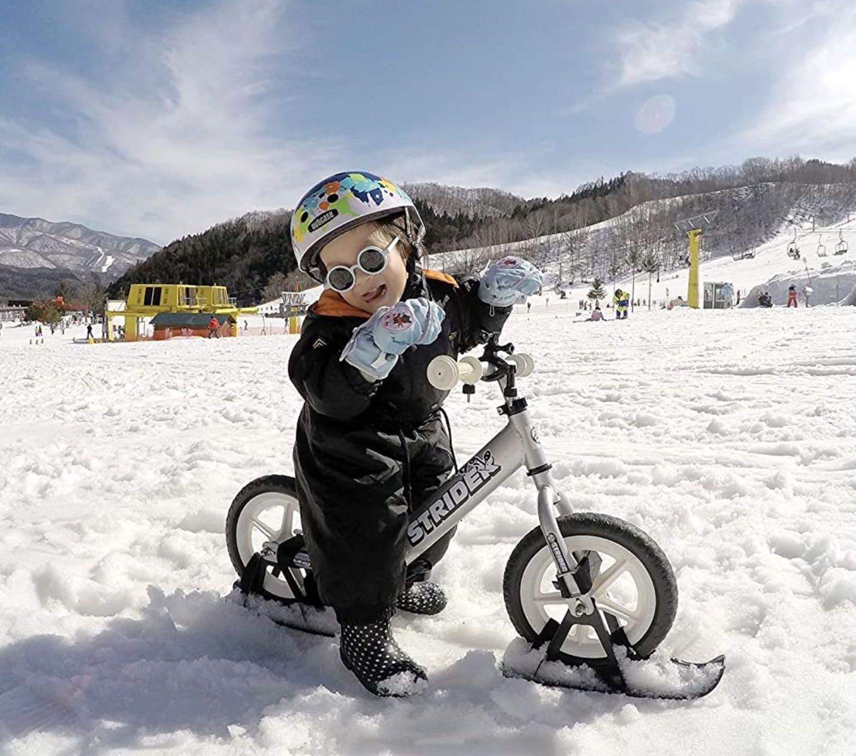 Niño montando sobre la nieve con su complemento de esquís para la bicicleta sin pedales Strider Sport