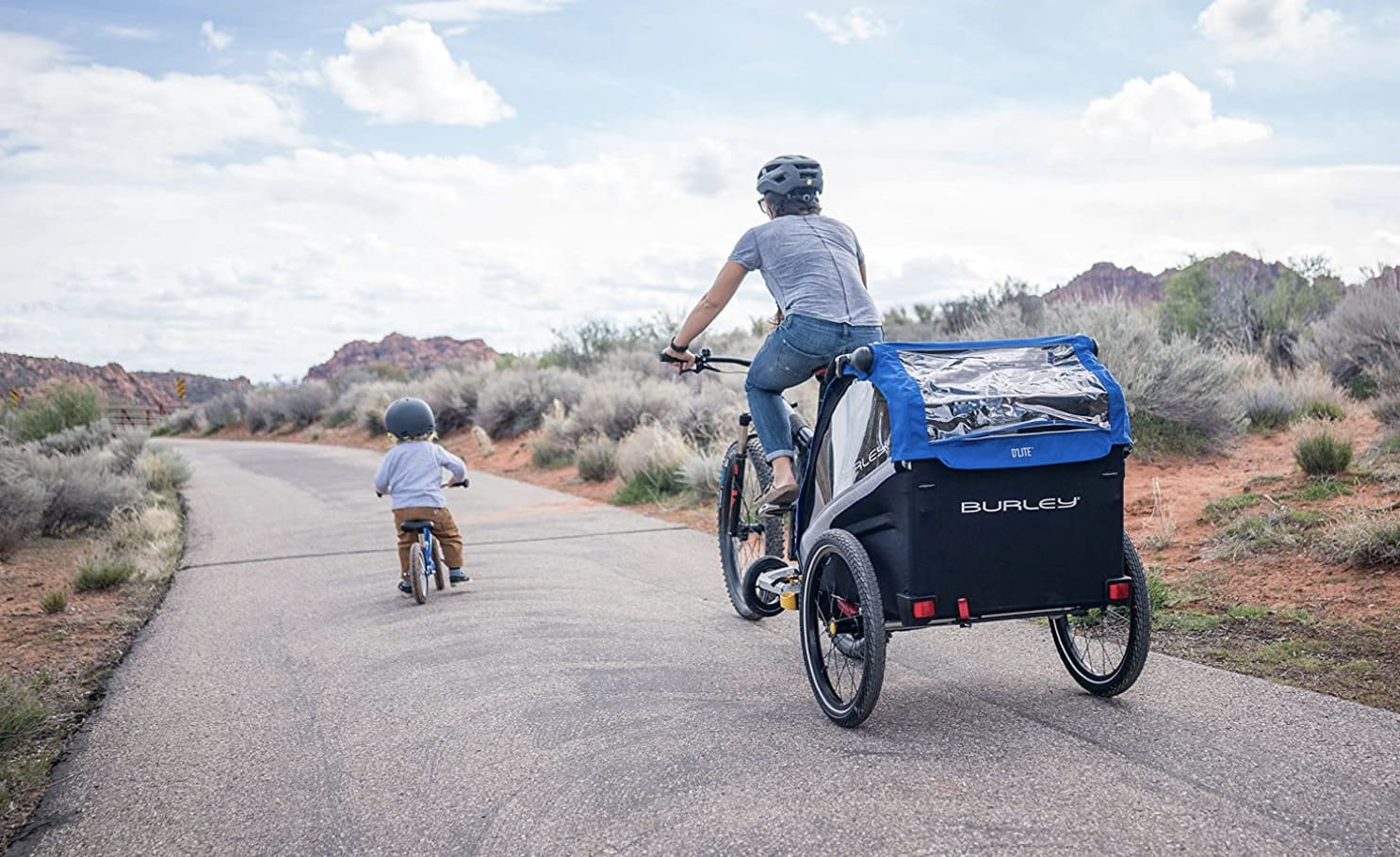 Madre e hijo con una bicicleta sin pedales y un remolque de bicicleta para niños