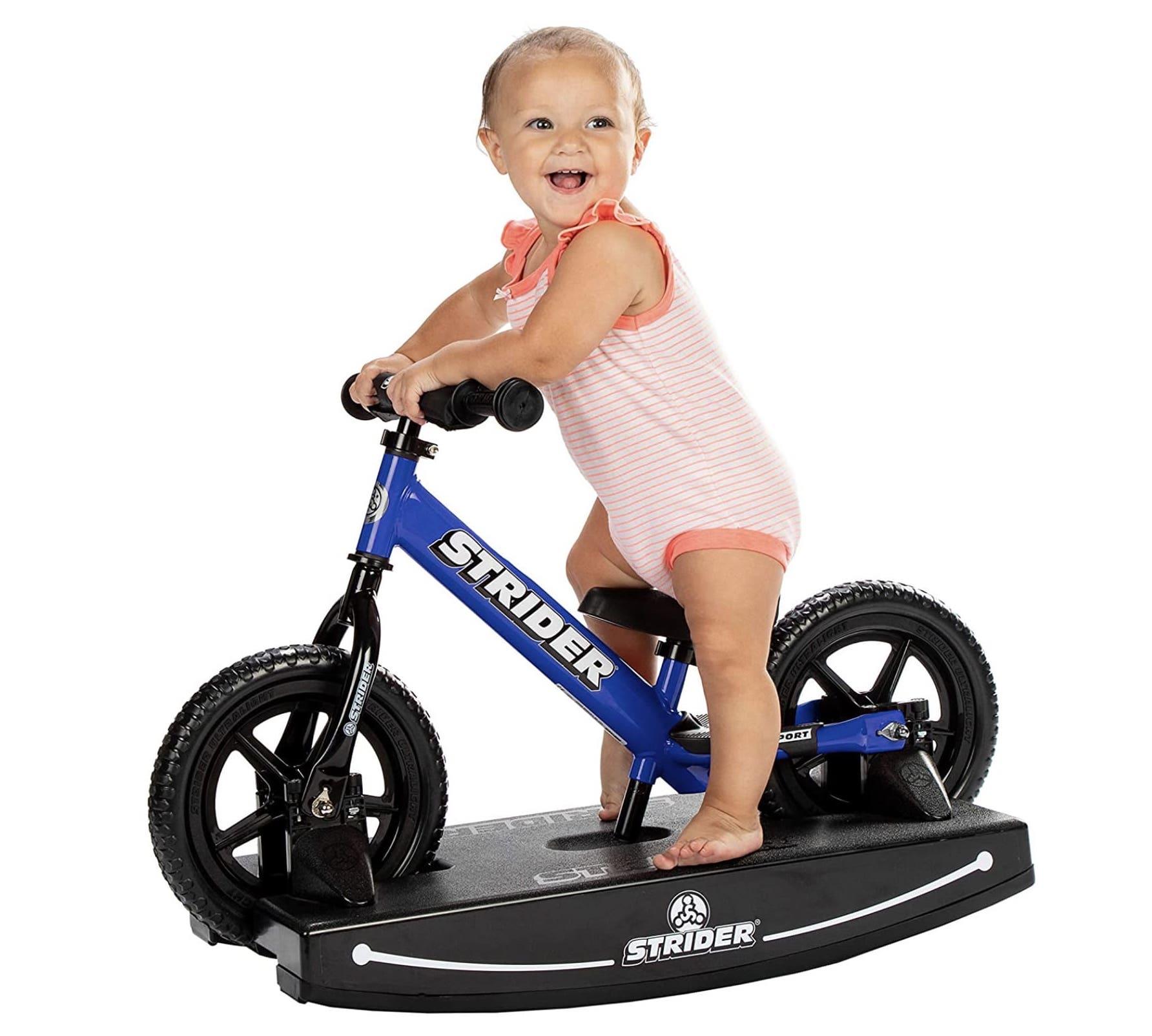 niña sobre la mecedora de la bicicleta sin pedales Strider Sport
