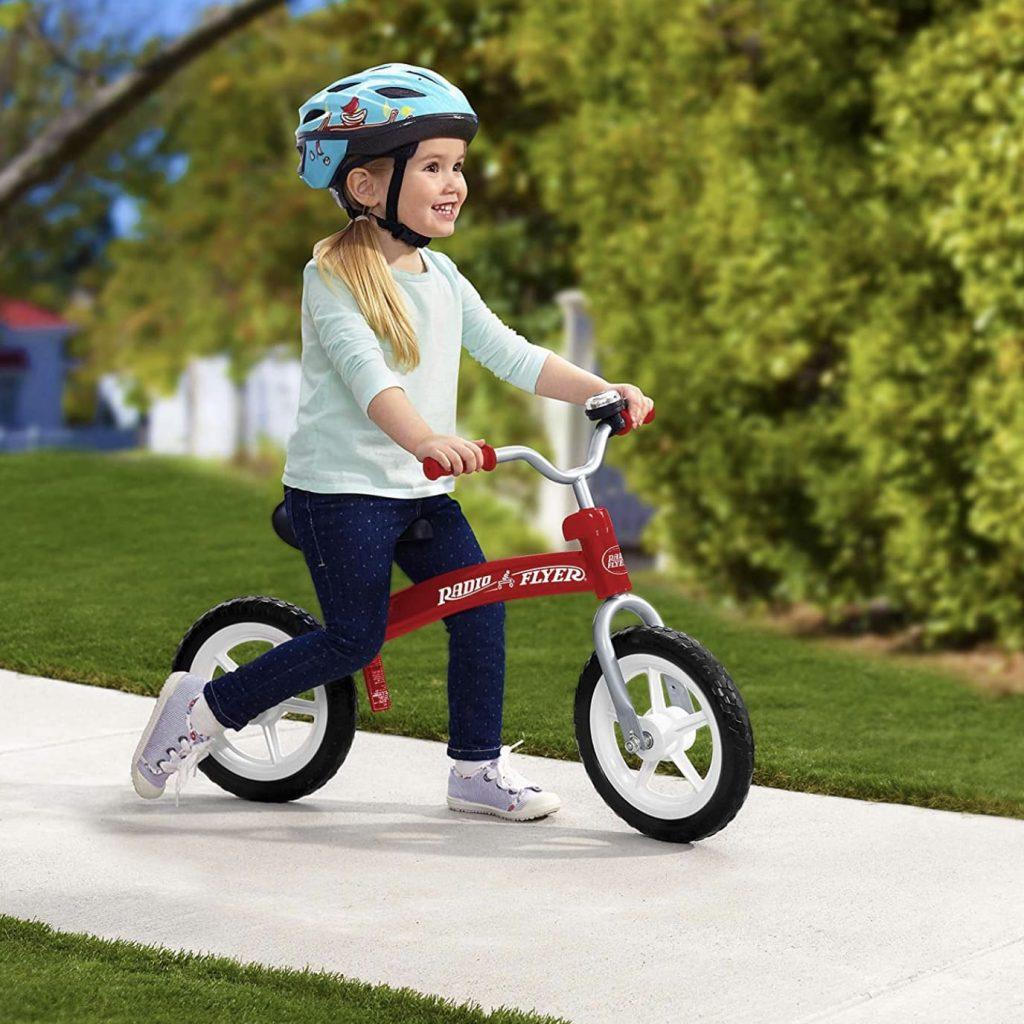 Niña montada sobre su bicicleta sin pedales