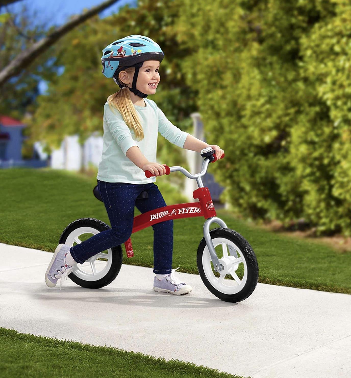 Niña conduciendo su bicicleta sin pedales Radio flyer