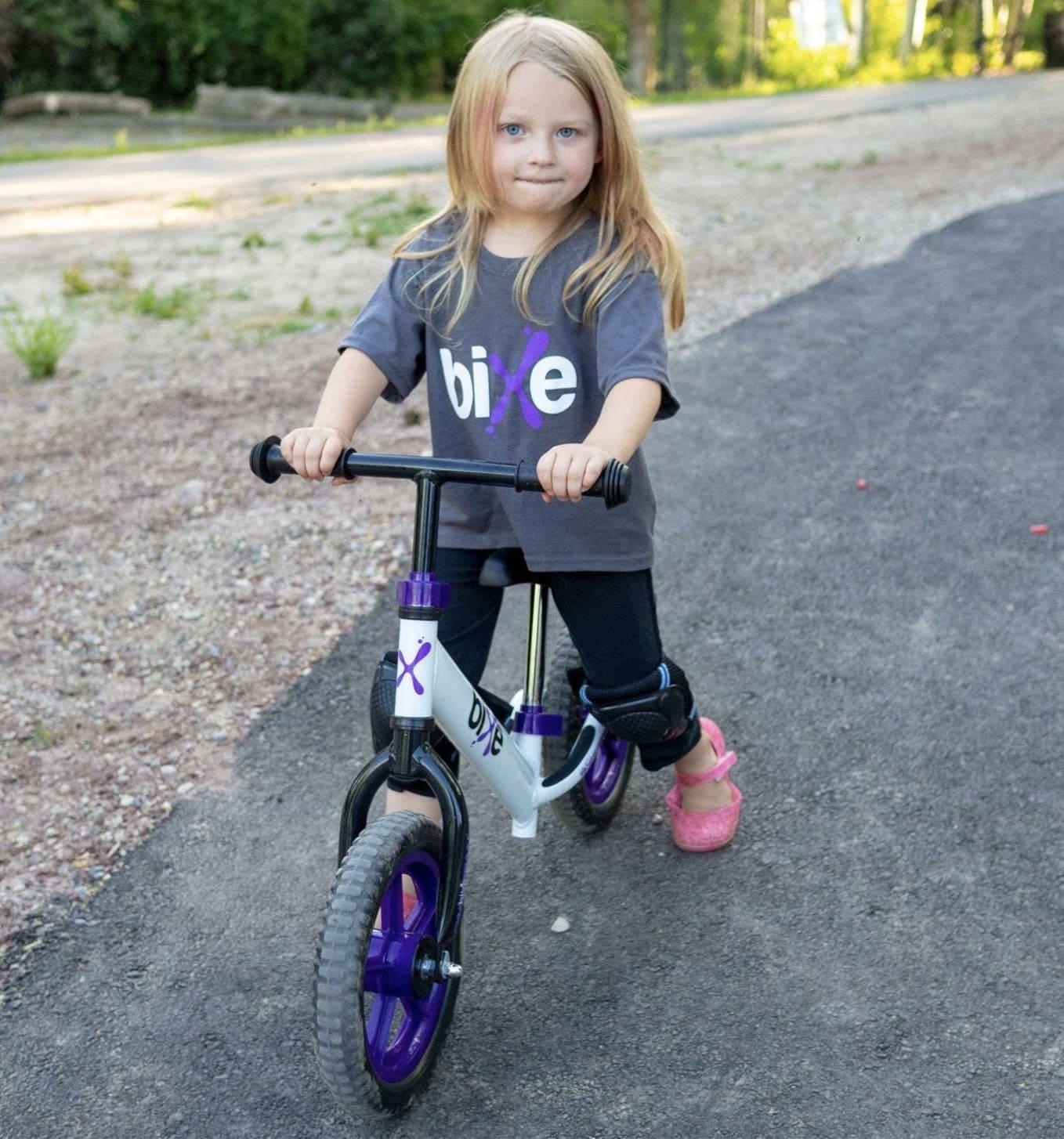 Niña conduciendo su bicicleta de equilibrio