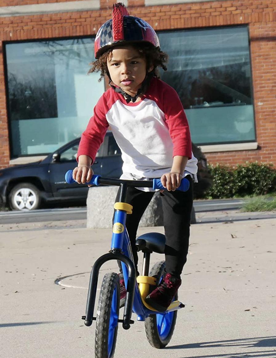 Niño sobre el reposapies de su bicicleta sin pedales Gomo