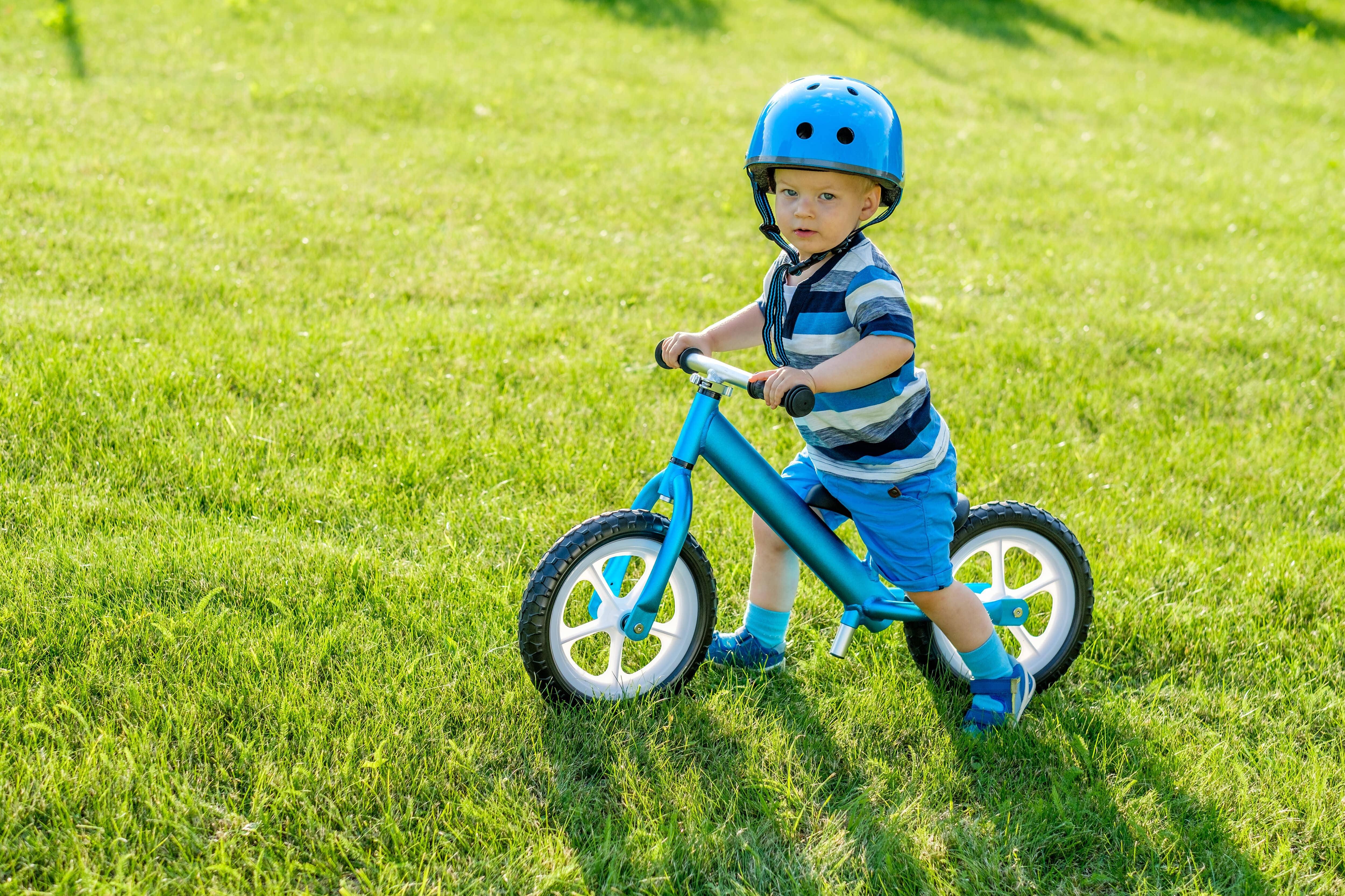 Niño pequeño montando sobre su bicicleta sin pedales azul