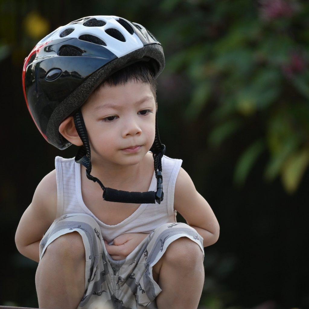 Niño con casco de bicicleta para niño que le queda grande