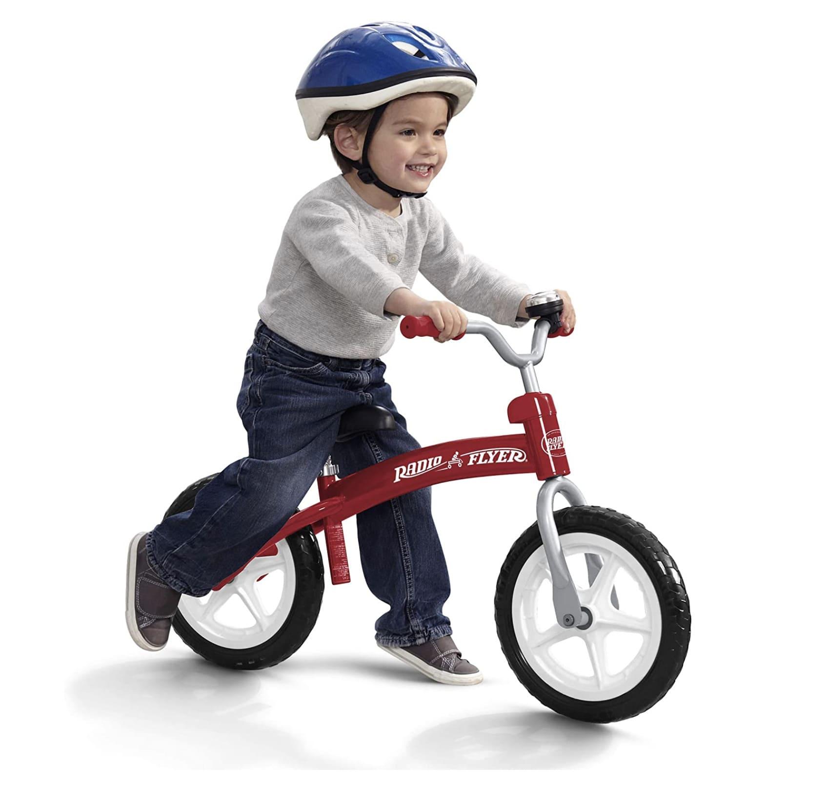 Niño llevando su bicicleta de equilibrio Radio Flyer