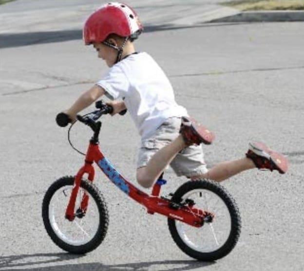 Niño deslizándose con su bicicleta son pedales