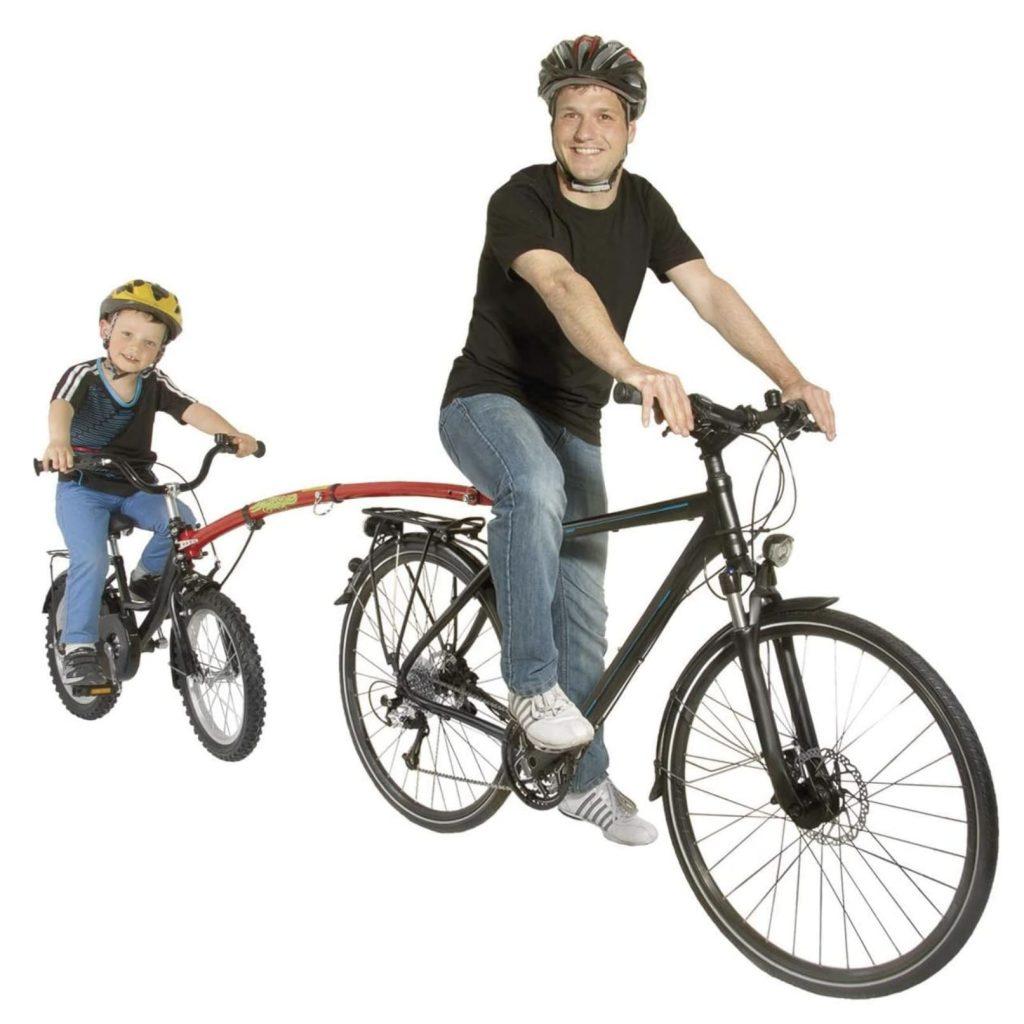 Padre remolcando con la barra de remolque para bicicleta a su hijo