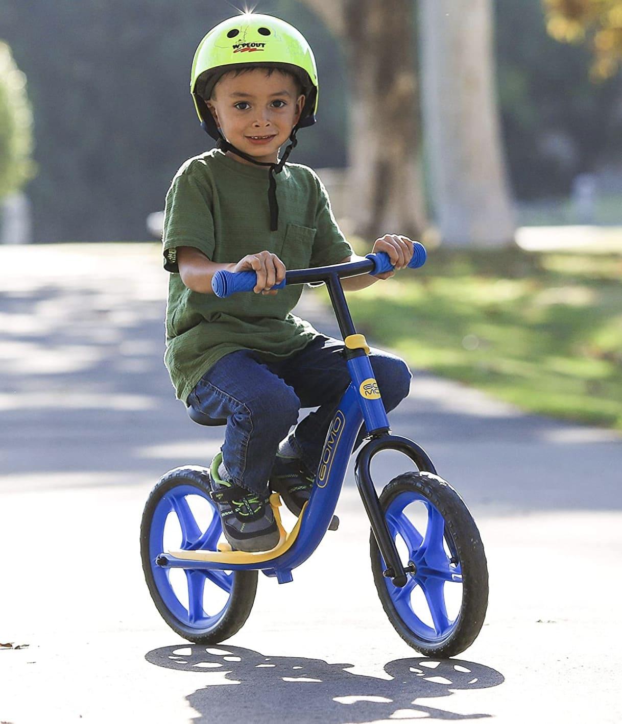 Niño con su pies en el reposapies de la bicicleta sin pedales GOmo