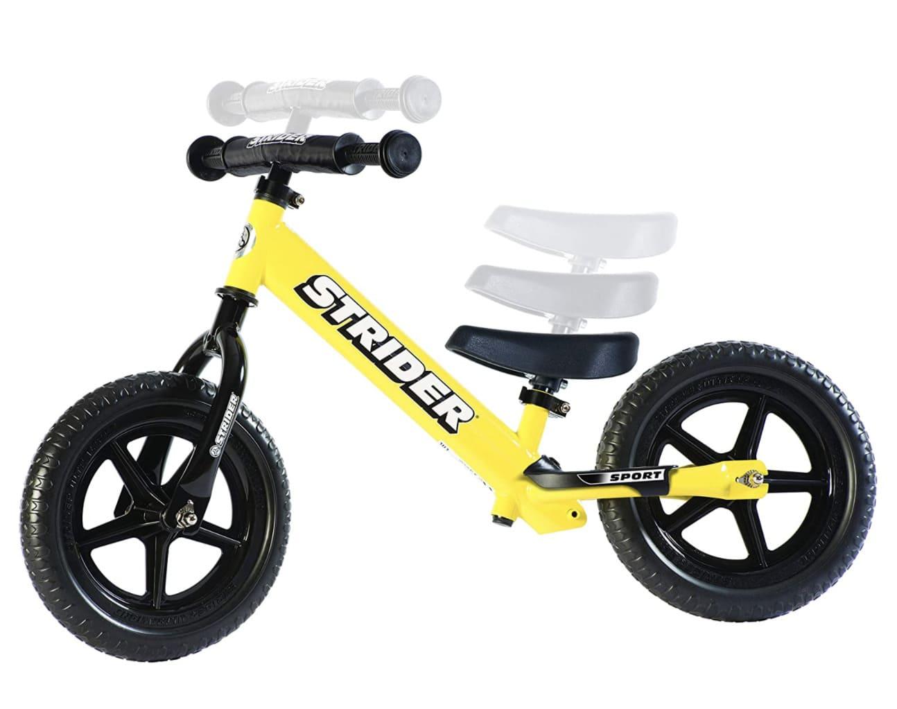 Niña muy pequeña conduciendo su bicicleta sin pedales Strider Sport