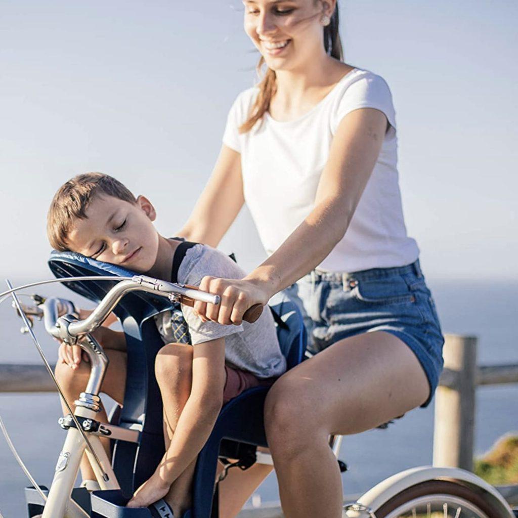 niño durmiendo en su silla bebe weeride safe front deluxe mientras su madre le lleva en bici