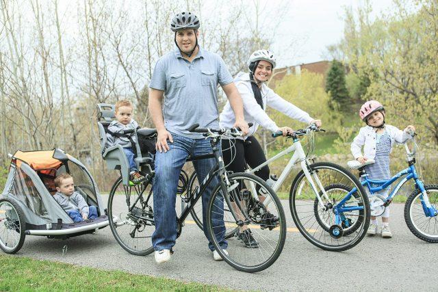 Familia viajando con sus hijos con accesorios para llevar niños en bicicleta