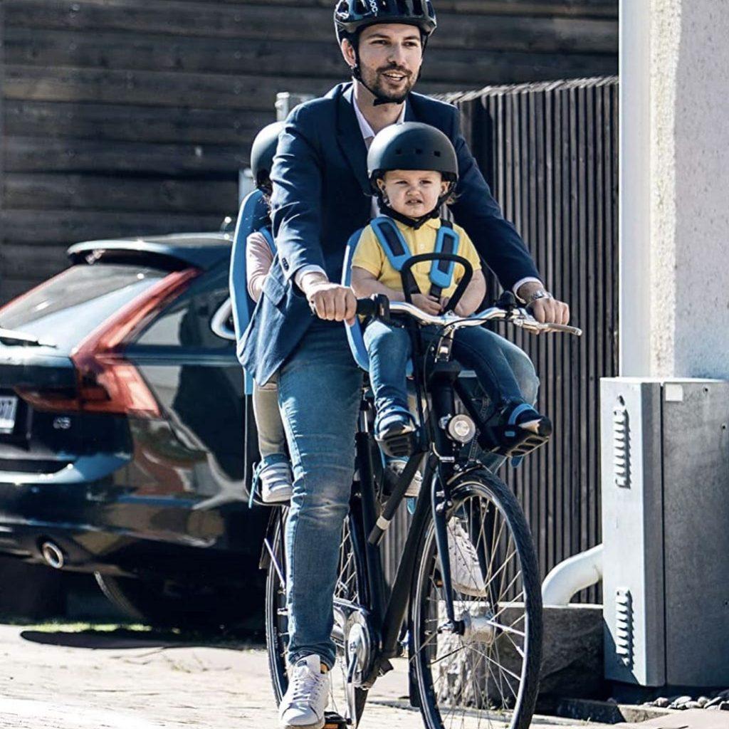 Padre llevando a su hijo en la sillita portabebe Thule Yepp Mini